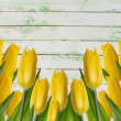 图库照片: Yellow tulips on wooden background