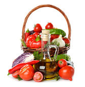 Vegetables in a basket and olive oil — Stock Photo
