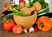 Wooden mortar and fresh vegetables — Stock Photo