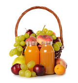 Various fruit in a basket and juice — Stock Photo
