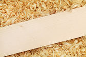 Wooden board diagonally placed on the shavings (with copyspace) — Stock Photo