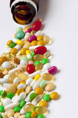 Viele bunte medikamente verschütten aus der flasche — Stockfoto