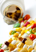 Many colorful medicines spilling out of a bottle — Stock Photo