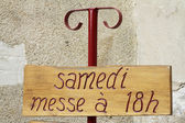"Wooden panel: ""Saturday Mass at 18 hours."" Saint-Germain Church in La Ferte-Loupière. — Stock Photo"