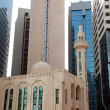 Mosque in front of modern buildings — Stock Photo