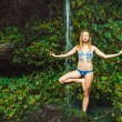 Woman Doing Yoga near Tropical Waterfall — Stock Photo #13844093
