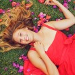 Beautiful Young Woman Lying in Flowers — Stock Photo #13844135