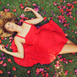 Beautiful Young Woman Lying in Flowers — Stock Photo #13844138