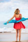 Krásná dívka v červených šatech na pláži. cestování a dovolená. — Stock fotografie
