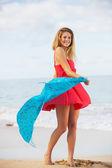 美丽的女孩,在沙滩上的红裙子。旅游和度假. — 图库照片