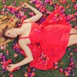 Beautiful Young Woman Lying in Flowers — Stock Photo #13987563