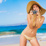 mujer hermosa en la playa con cámara — Foto de Stock
