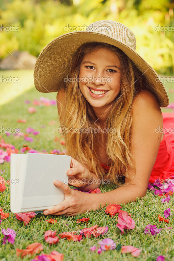 Beautiful Young Woman Reading a Book Outside on the Grass — Stock Photo #13987557