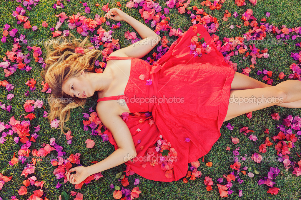 Beautiful Young Woman Lying on Grass with Flowers — Stock Photo #13987563