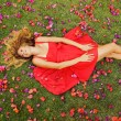 Beautiful Young Woman Lying in Flowers — Stock Photo #14319823