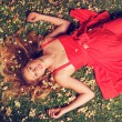 Beautiful Young Woman Lying in Flowers — Stock Photo #14319879
