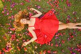 Bellissima giovane donna sdraiata in fiori — Foto Stock