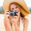 Beautiful Woman at the Beach with Camera — Stock Photo