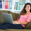 Happy young woman using a laptop computer — Stock Photo