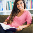 Happy young woman reading a book — Stock Photo #30119635