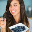 Beautiful woman eating blueberries — Photo