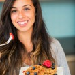 Woman eating Waffles with Fresh Fruit — Stock Photo #30915409