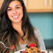 Woman eating Waffles with Fresh Fruit — Stock Photo #30940311