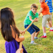Stock Photo: Kids Playing Tug of War On Grass