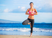 Woman practicing yoga at sunset — Stock Photo