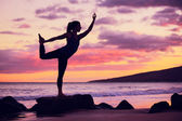 Woman practicing yoga on the beach at sunset — Stock Photo