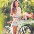 Beautiful young woman on bike — Stock Photo #32589945