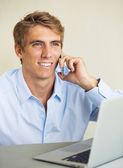 Young Man Working on Laptop Computer Talking on Phone — Stock Photo