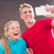Young attractive athletic couple taking photo of themselves with — Stock Photo #34833941