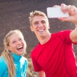 Young attractive athletic couple taking photo of themselves with — Stock Photo #34836927