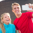Young attractive athletic couple taking photo of themselves with — Stock Photo #34837017