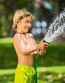 Child, boy or kid plays with water hose outdoors — Stock Photo