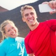 Young attractive athletic couple taking photo of themselves with — Stock Photo #34898797