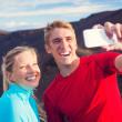 Young attractive athletic couple taking photo of themselves with — Stockfoto