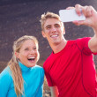 Young attractive athletic couple taking photo of themselves with — Foto de Stock