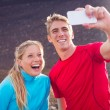 Young attractive athletic couple taking photo of themselves with — Stock Photo