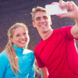 Young attractive athletic couple taking photo of themselves with — 图库照片