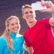 Young attractive athletic couple taking photo of themselves with — Stock Photo #35183853