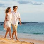 Romantic happy couple walking on beach at sunset. Smiling holdin — Stock Photo #35185413