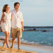 Romantic happy couple walking on beach at sunset. Smiling holdin — Stock Photo