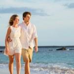 Romantic happy couple walking on beach at sunset. Smiling holdin — Stock Photo