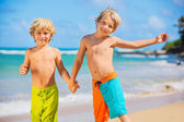 Happy young kids playing at the beach on summer vacation — Stock Photo