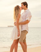 Happy romantic couple on the beach at sunset embracing each othe — Foto de Stock
