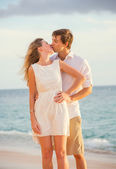 Happy romantic couple kissing on the beach at sunset, Man and wo — Stock Photo