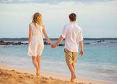 Romantic happy couple walking on beach at sunset. Smiling holdin — Foto de Stock
