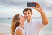 Happy romantic couple on the beach taking photo of themselves wi — Stock Photo